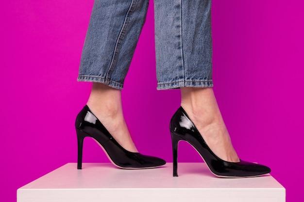 Nahaufnahme der füße einer frau in den schwarzen schuhen auf einem rosa hintergrund