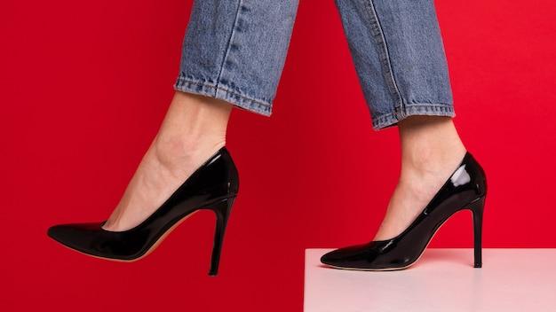 Nahaufnahme der füße einer frau in den schwarzen schuhen auf einem roten hintergrund