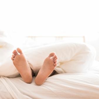 Nahaufnahme der füße einer person, die auf bett liegen
