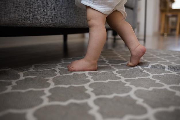 Nahaufnahme der füße eines babys auf einem grauen teppich in einem raum