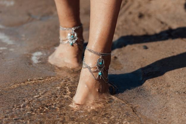 Nahaufnahme der füße in boho-schmuck einer frau, die barfuß am strand spazieren geht