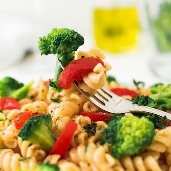 Nahaufnahme der gabel mit brokkoli; tomaten und fusilli