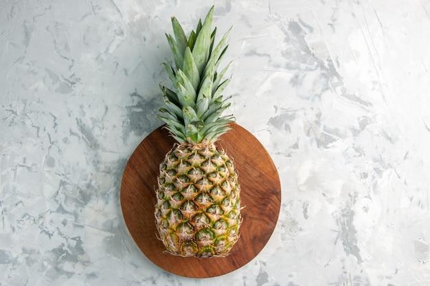 Nahaufnahme der ganzen frischen goldenen ananas auf schneidebrett auf marmoroberfläche