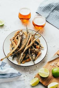Nahaufnahme der gebratenen fischsardelle in einem teller neben bier in gläsern und limette auf einem brett