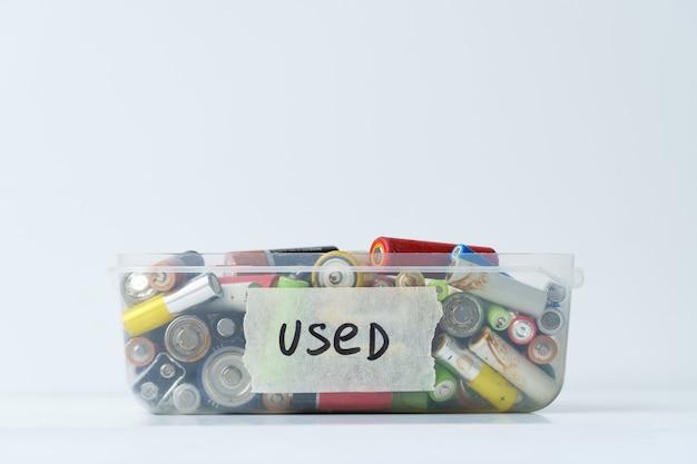 Nahaufnahme der gebrauchten batterie in kunststoffbehälter über der weißen wand elektronisches sondermüllkonzept