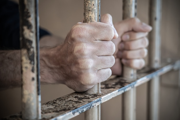 Nahaufnahme der gefangenenhände im gefängnis