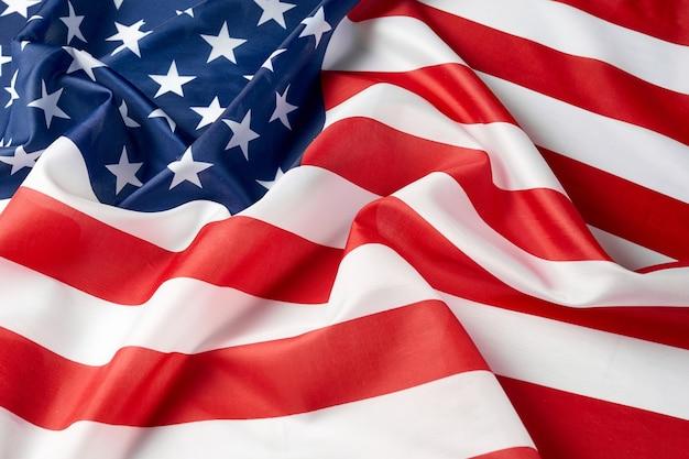 Nahaufnahme der gekräuselten amerikanischen flagge. gebogene flagge der satinbeschaffenheit der usa. gedenktag oder 4. juli.