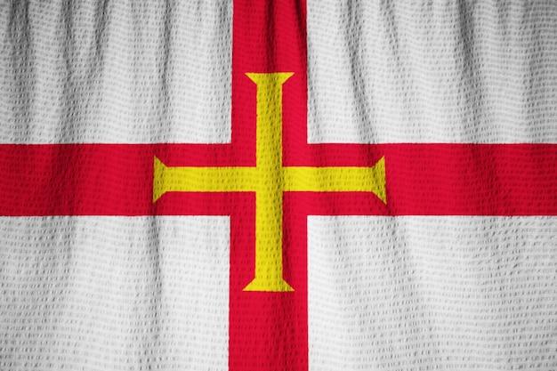 Nahaufnahme der gekräuselten guernsey-flagge, guernsey-flagge, die im wind durchbrennt