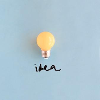 Nahaufnahme der gelben glühlampe mit ideenwort auf blauem hintergrund