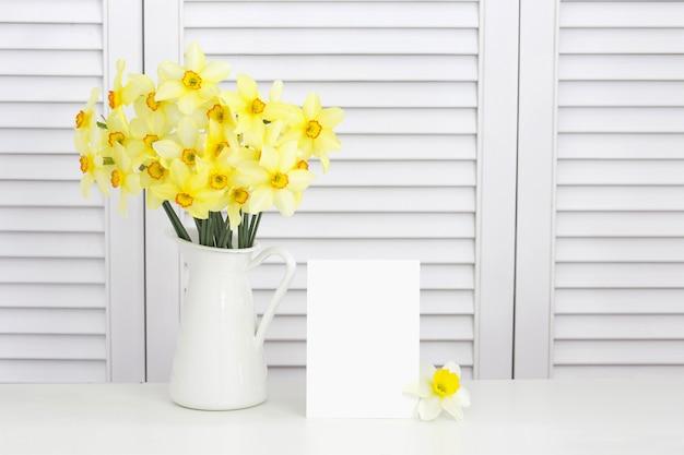 Nahaufnahme der gelben narzissenblume in der vase über weißen fensterläden