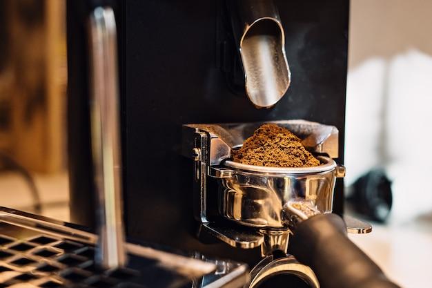 Nahaufnahme der gemahlenen kaffeebohne in der kaffeemaschine