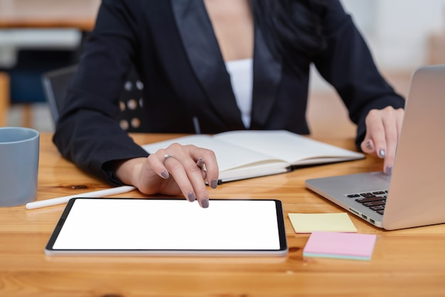 Nahaufnahme der geschäftsfrau, die den stift hält, der unter verwendung des leeren weißen bildschirms der tablette und des tastaturlaptops im büro arbeitet.