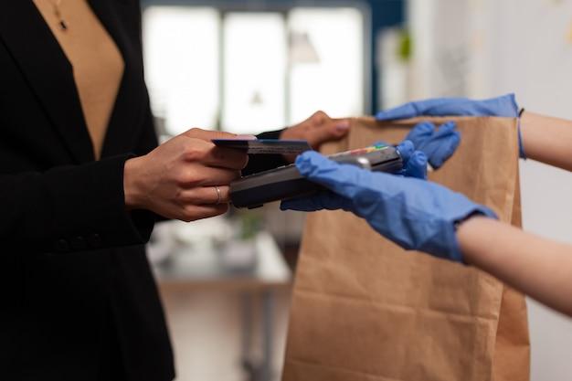 Nahaufnahme der geschäftsfrau, die essen zum mitnehmen mit kreditkarte mit kontaktlosem pos-service bezahlt?
