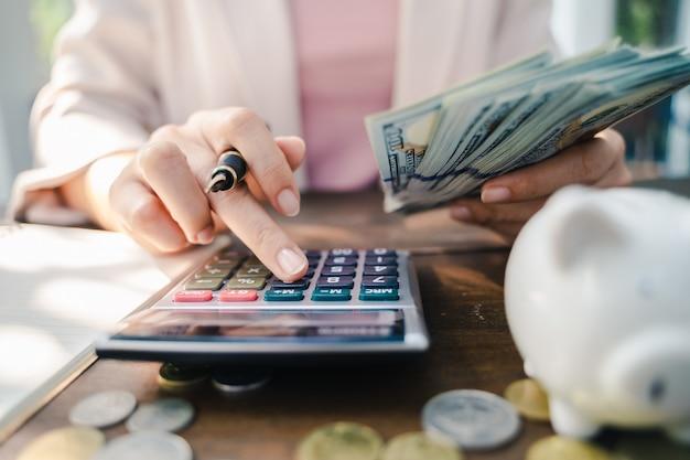 Nahaufnahme der geschäftsfrau mit dem taschenrechner, der geld zählt. geld sparen und finanzielles konzept