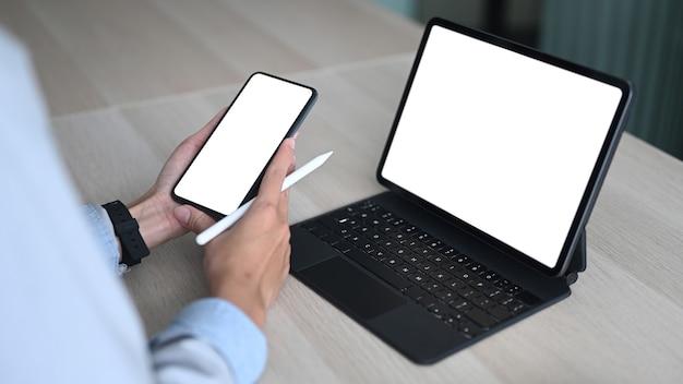 Nahaufnahme der geschäftsfrau mit smartphone beim sitzen vor dem computer-tablet am schreibtisch.