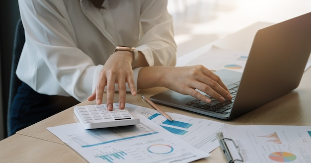 Nahaufnahme der geschäftsfrau oder buchhalterhand mit bleistift, die am rechner arbeitet, um finanzdatenbericht, buchhaltungsdokument und laptop-computer im büro zu berechnen, geschäftskonzept.