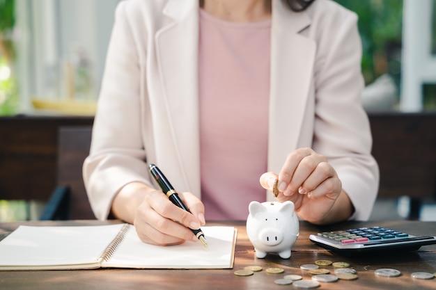 Nahaufnahme der geschäftsfrauenhand, die geldmünze in sparschwein für das sparen von geld setzt. geld sparen und finanzielles konzept