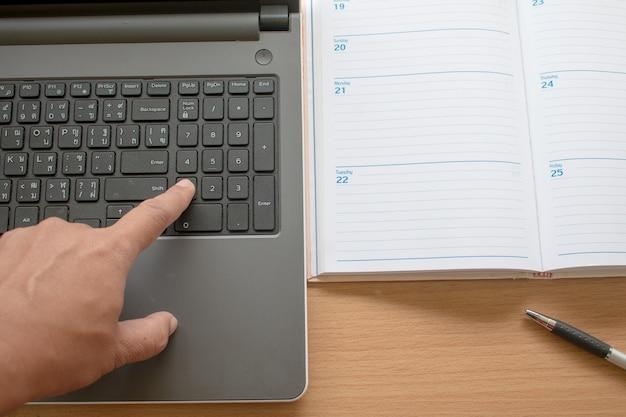 Nahaufnahme der geschäftshand zeigt auf die tastatur des laptops arbeiten am laptop und organisieren