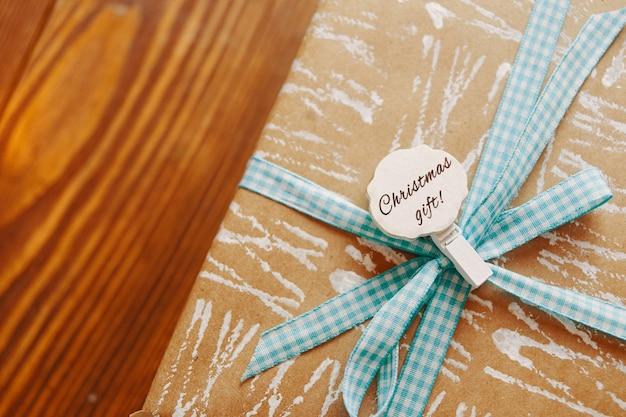 Nahaufnahme der geschenkbox mit band und abzeichen auf holztisch-pin mit weihnachtsaufschrift weißes patte...