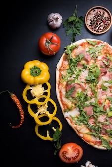Nahaufnahme der geschmackvollen rohen pizza mit scheiben des grünen pfeffers; tomate; knoblauch; chili und trockene gewürze