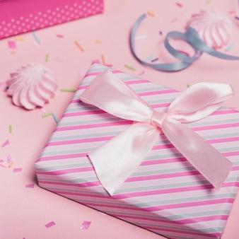 Nahaufnahme der gestreiften geschenkbox mit satinbogen gegen rosa hintergrund