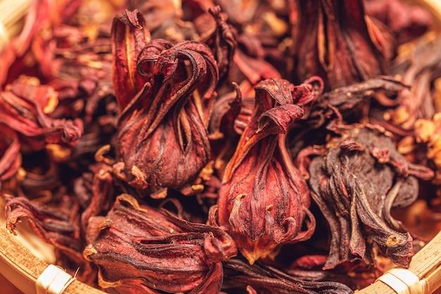 Nahaufnahme der getrockneten rosellenblume in der holzschale für kräutertee oder rosellasaft