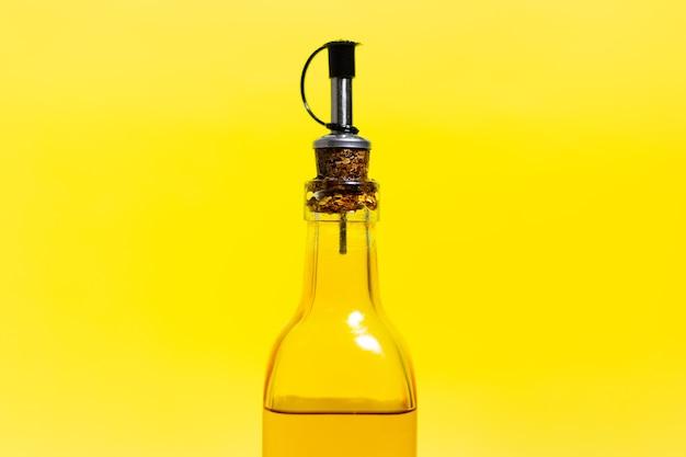 Nahaufnahme der glasflasche mit olivenöl, verschlossen mit spezialkappe, isoliert auf gelb