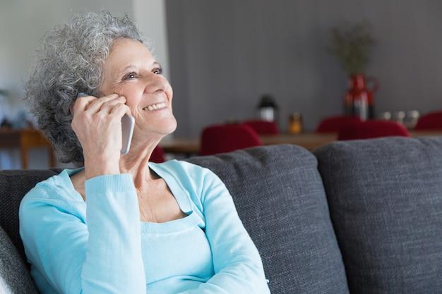 Nahaufnahme der glücklichen älteren frau, die auf smartphone spricht