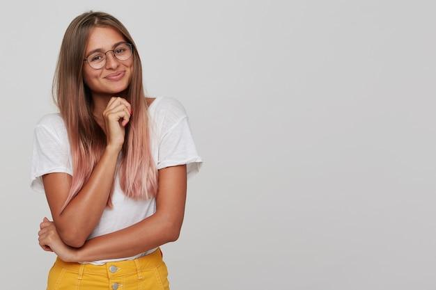 Nahaufnahme der glücklichen attraktiven jungen studentin mit langem gefärbtem pastellrosa haar trägt t-shirt und brille, die mit gefalteten händen stehen und lokalisiert über weißer wand lächeln