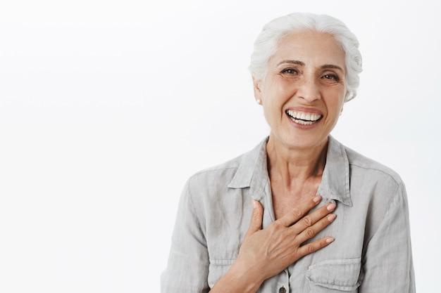 Nahaufnahme der glücklichen entzückenden alten dame, die lacht und lächelt