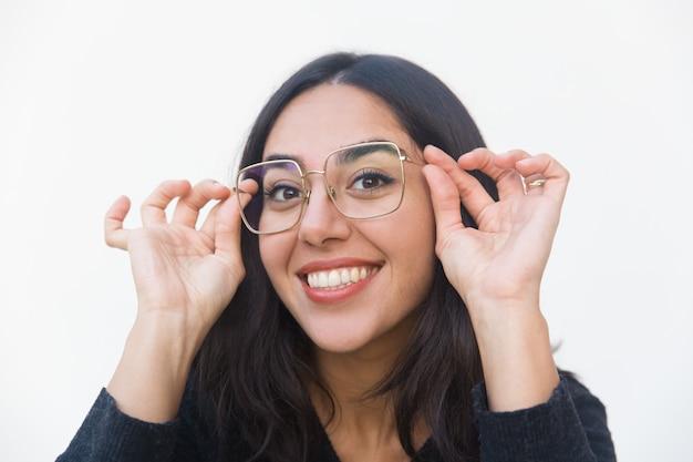 Nahaufnahme der glücklichen frohen frau, die gläser justiert