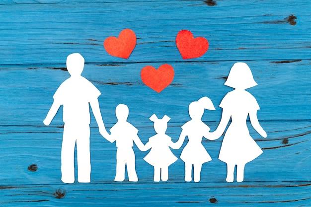 Nahaufnahme der glücklichen papierfamilie auf blauem hintergrund