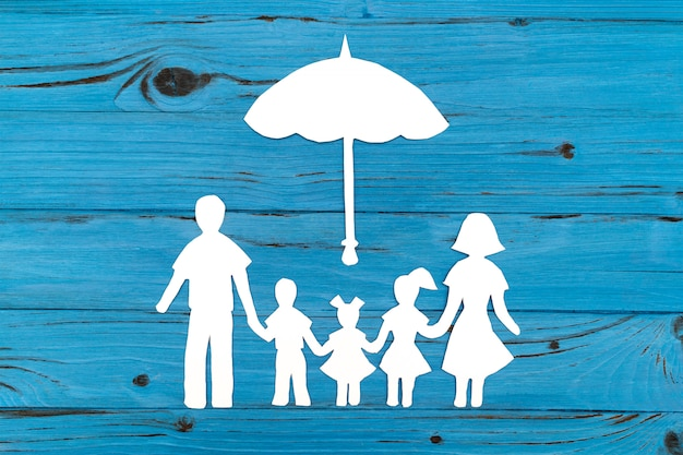 Nahaufnahme der glücklichen papierfamilie auf blauer oberfläche