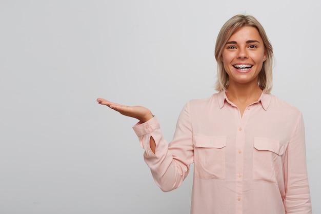 Nahaufnahme der glücklichen selbstbewussten blonden jungen frau mit zahnspangen auf zähnen trägt rosa hemd lächelnd und hält copyspace auf handfläche lokalisiert über weißer wand