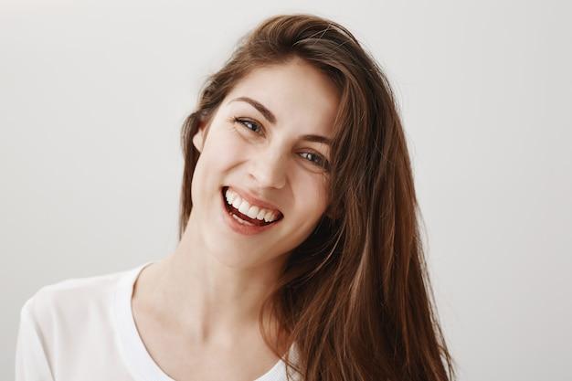 Nahaufnahme der glücklichen wunderschönen gesunden frau, die vorne lächelt und lacht