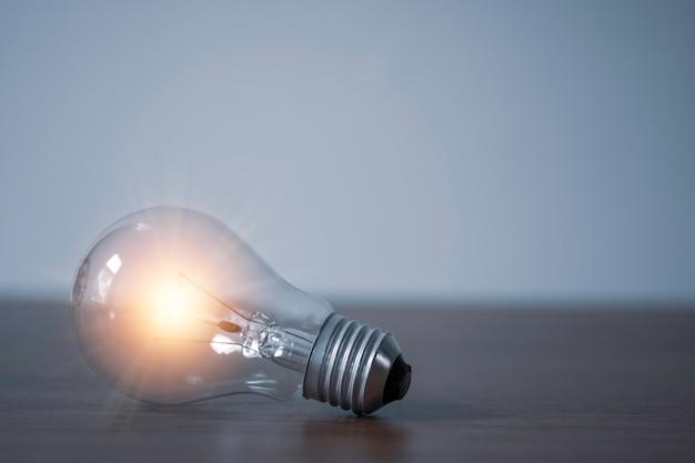Nahaufnahme der glühbirne mit dem orange leuchtenden auf dem tisch. kreatives ideenkonzept.