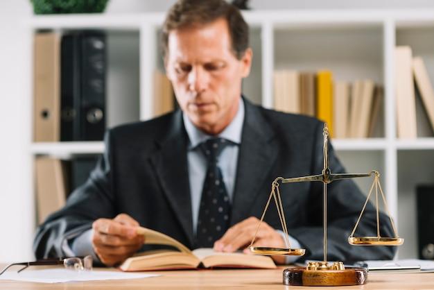 Nahaufnahme der goldenen skala vor rechtsanwaltlesebuch im gerichtssaal