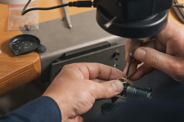 Nahaufnahme der goldschmiedehand, die kostbaren ring mit schönen edelsteinen verziert. professioneller juwelier, der den fertigen goldenen ring betrachtet. produktionskonzept für goldschmuck.