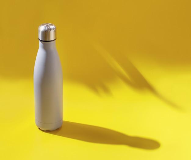 Nahaufnahme der grauen wiederverwendbaren stahlflasche auf gelbem hintergrund mit hartem licht