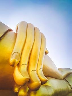Nahaufnahme der großen buddha-statue mit blauem himmel im wat tha muang thailand. die ikonischsten goldenen buddha-statuen