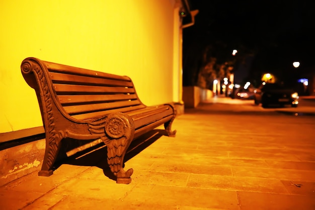 Nahaufnahme der grünen holzbank im stadtpark während des sonnenuntergangs. leere holzbank im stadtpark