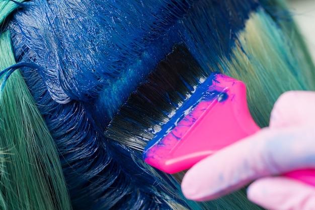 Nahaufnahme der haarfärbung bei schönheitssalon friseur mit rosa pinsel beim auftragen von blauer farbe
