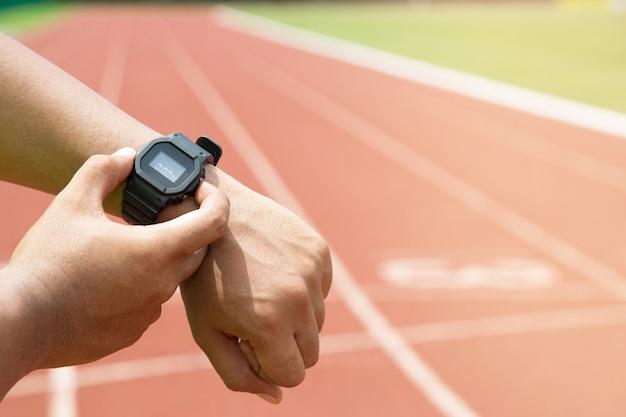 Nahaufnahme der hände athlet, der seine uhr überprüft race-timer-läufer, der bereit ist, auf der laufstrecke zu laufen.