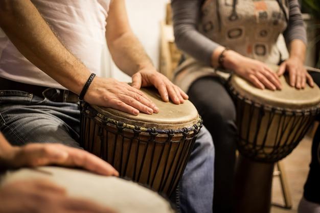 Nahaufnahme der hände auf afrikanischen trommeln, trommeln für eine musiktherapie