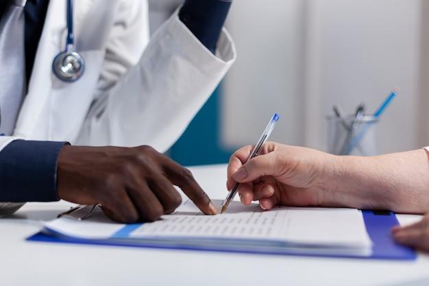 Nahaufnahme der hände auf dem schreibtisch in der gesundheitsklinik