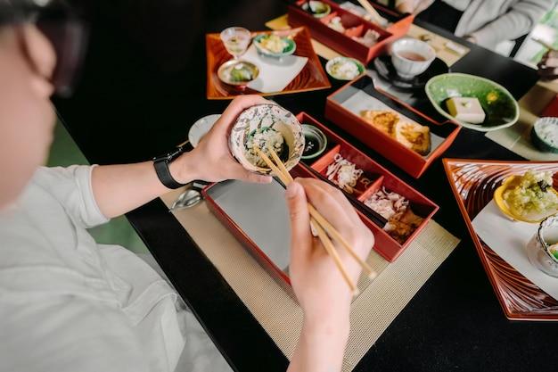 Nahaufnahme der hände beim essen mit stäbchen