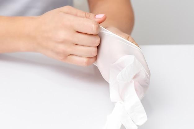 Nahaufnahme der hände der frau, die die weißen gummihandschuhe im maniküresalon anziehen.