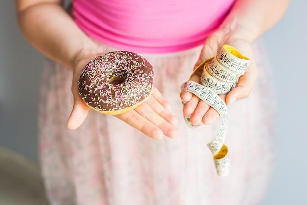 Nahaufnahme der hände der frau, die einen donut und ein maßband halten. das konzept der gesunden ernährung. diät.