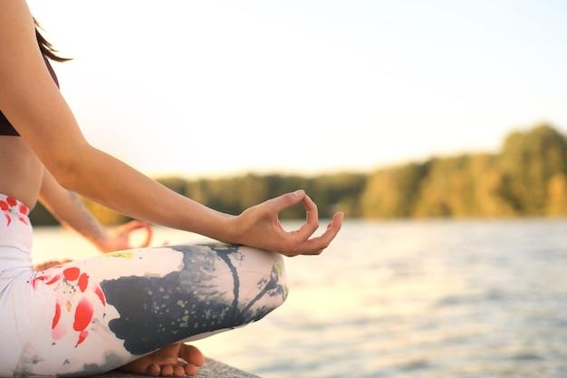 Nahaufnahme der hände der frau machen yoga im freien, lotus-pose. gesundes und yoga-konzept.