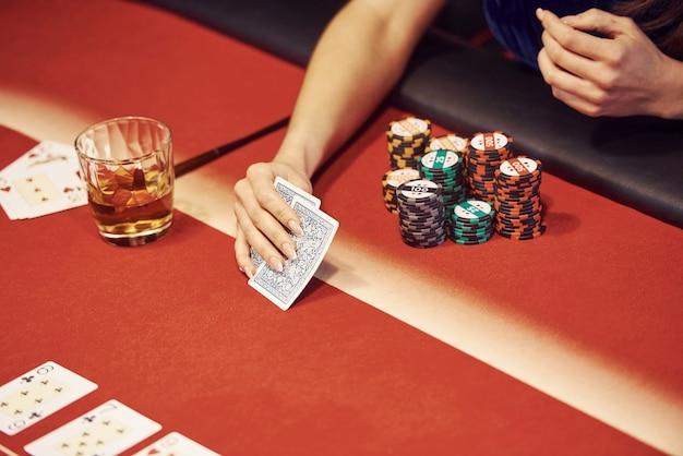 Nahaufnahme der hände der frau. mädchen spielt pokerspiel durch tabelle im kasino